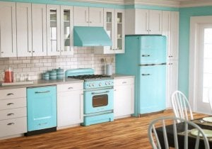 A kitchen with a wood floor and vintage metal appliances is seen at an angle that shows cabinets, dishwasher, stove, and fridge (which are painted sky blue).