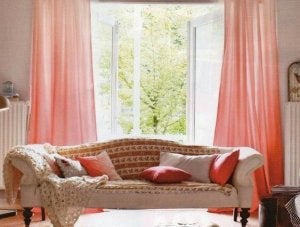 Pink curtains spread apart in front of open windows looking out onto a green outdoor space.