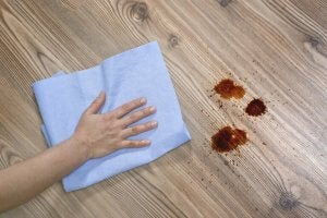 A person cleaning up a mess on a wooden floor with a rag, which is important if you want to care for wood furniture.