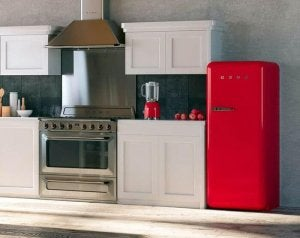 A kitchen with wooden floors at an angle that we can see its metal stove, white cabinets, and red refrigerator, painted with stainless steel paint.