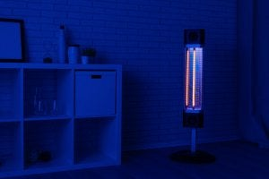 A space heater is on in a room bathed in blue light.