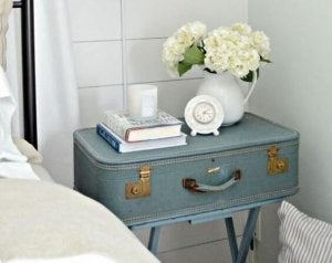 A picture showing a vintage suitcase being used as a nightstand beside a bed, with a couple books and a vase on top of it.