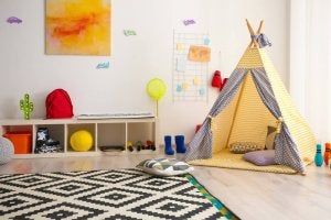 A picture showing how to decorate a toy library: with a tent, a rug, and some fun wall decorations.