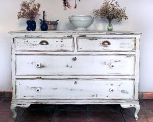 A vintage dresser with flaking white paint is in the hallway to a house, with various flower vases on top of it.