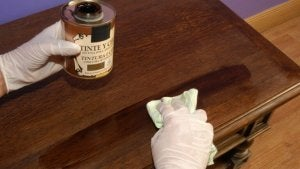 A person with latex gloves on their hands is wiping their furniture with wood wax.