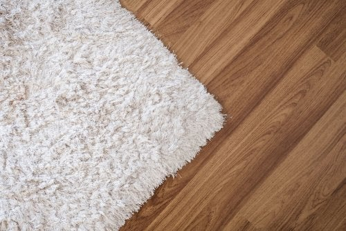 A white long pile woolen rug on a timber floor