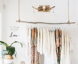 An eco-friendly clothes rack with light clothes hanging from it.