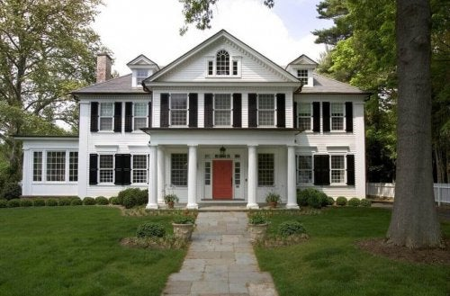 A white colonial house with a large yard.