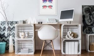 A chic desk with a lot of small decorations sitting in and on top of it.