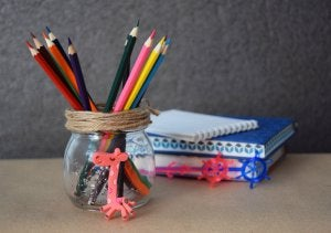 A glass jar containing colored pencils.