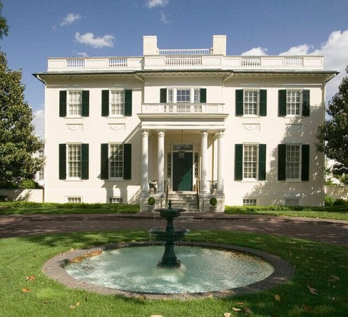 A grand, white colonial house with a wrap-around driveway.