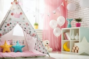 A kids playroom with a tent and stuffed animals.