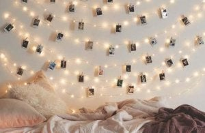 A photo mural is hanging on a wall along string lights.