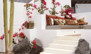 An Ibiza style terrace with steps and cushions.