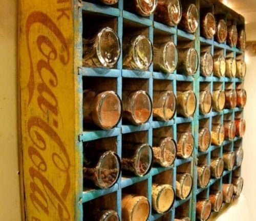 A spice rack made out of a wooden soda box.