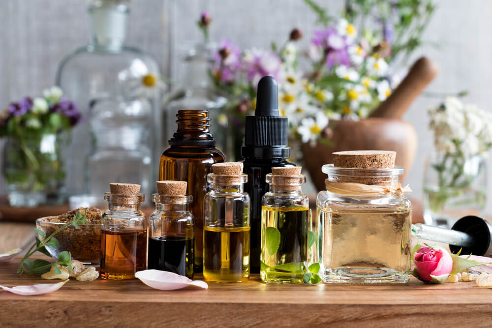 An assortment of essential oils on a wooden slab.