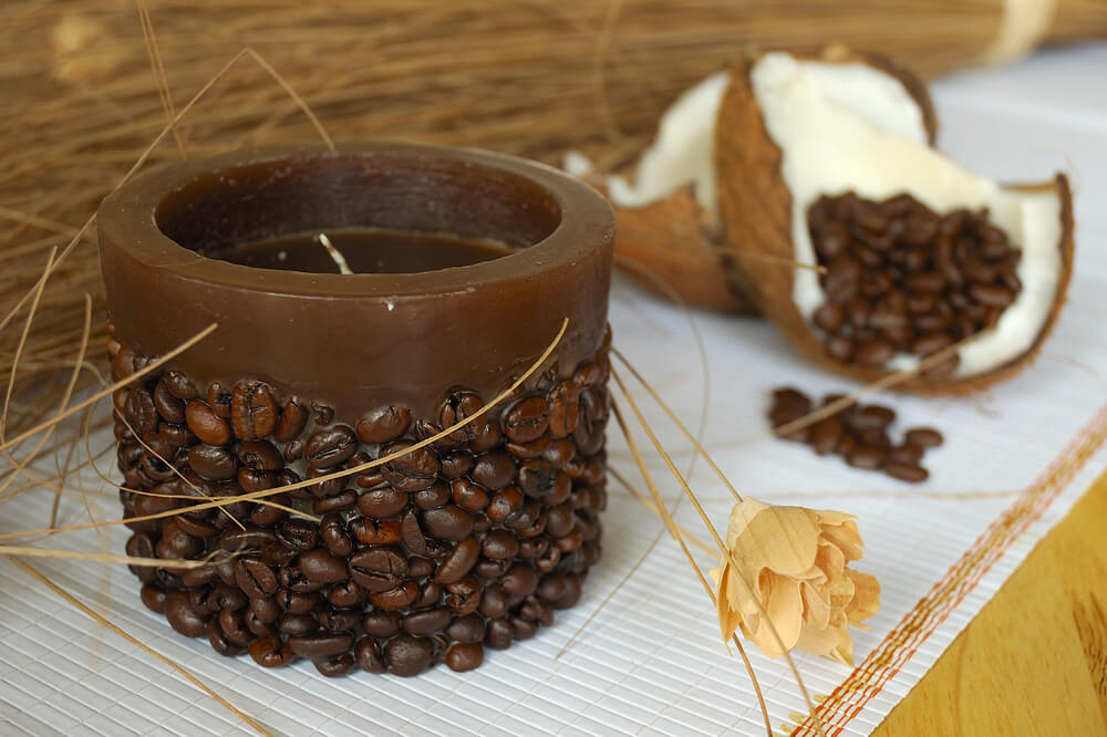 A scented candle with coffee beans on it.