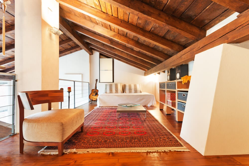 A loft with a slanting wood ceiling.