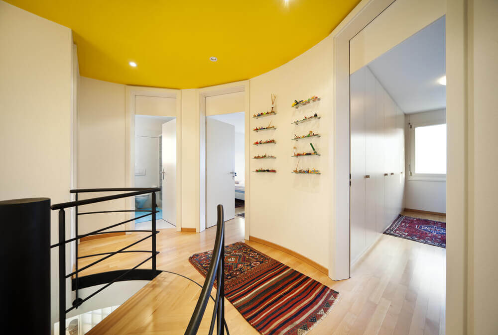 A simple ceiling design with yellow paint and lights installed within.