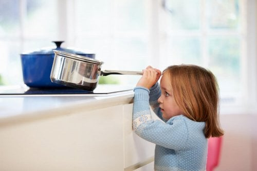 A child pulling a pot from the stove.