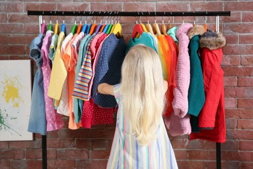 A little person looking through hanging garments at their walk-in closet..