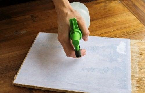 A person spraying a print.