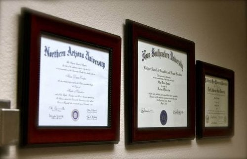 Three academic diplomas on the wall.