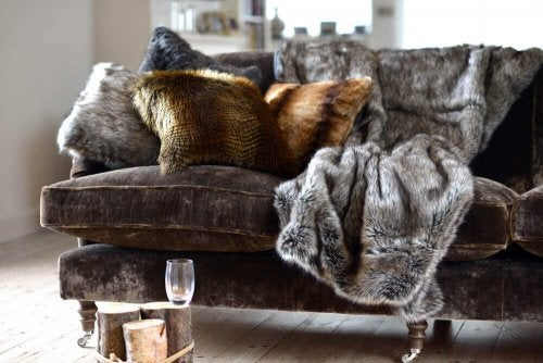 A faux fur blanket on a grey couch.