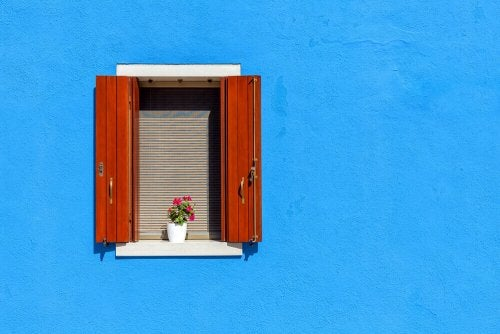 Rustic shutters in a blue facade.