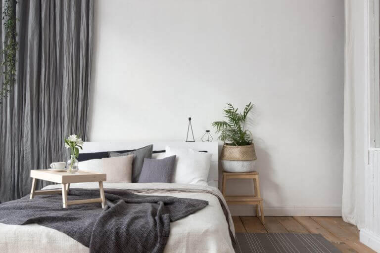 Use of gray textiles and natural wood in a bedroom