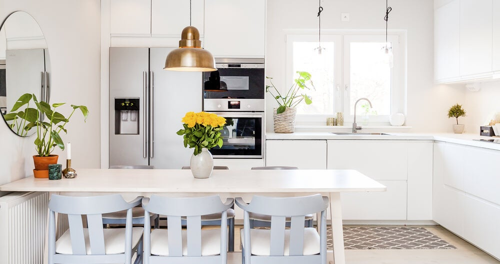 A white themed kitchen with table and chairs