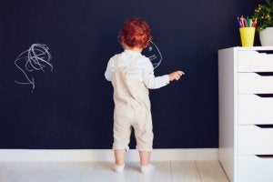 A toddler drawing on a chalkboard wall.