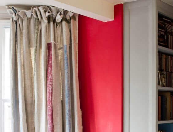 Curtains painted using chalk paint shown against a red feature wall