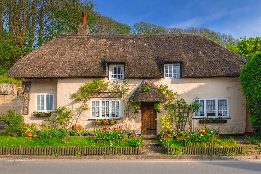 An English cottage with a thatched roof and climbing roses