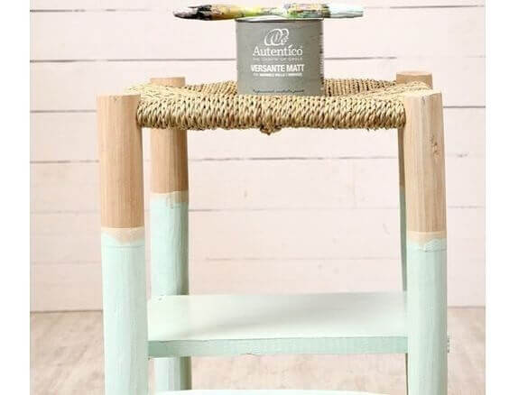 A painted timber stool with a natural fiber seat