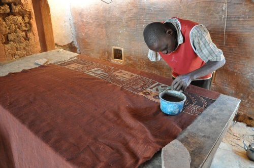 An man working on a roll of mud cloth.