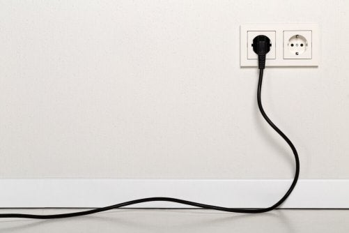 An electrical cable plugged into a wall.