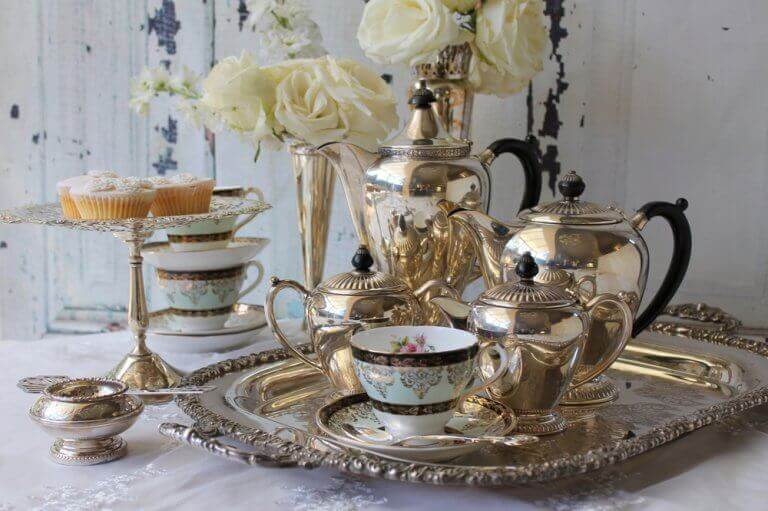 A typical English afternoon tea complete with gold service, fine china and cupcakes