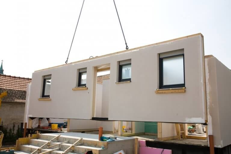 A completed wall is lifted into place for a modular home