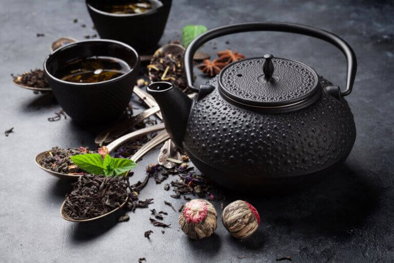 A black ceramic teapot with dried leaves and spices