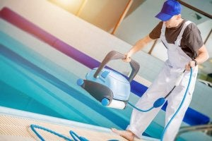 A man is holding a robot pool cleaner.