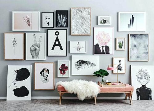 A wall full of paintings and pictures.