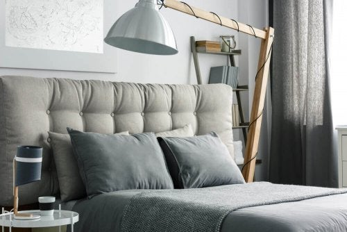 A large bed with gray headboard and linens