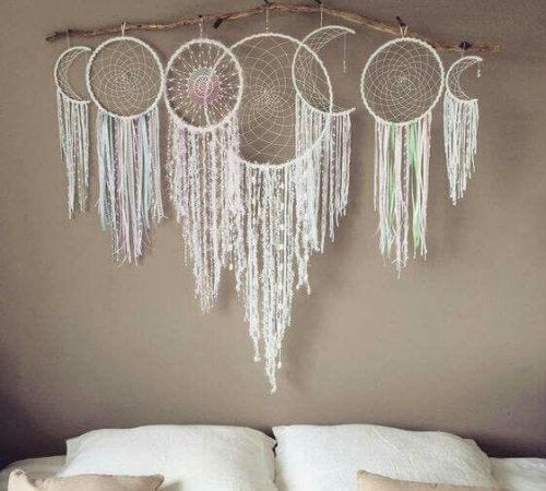 Seven dreamcatchers above a bed.