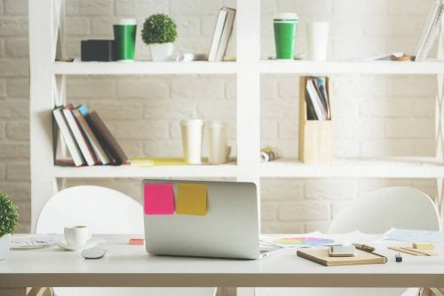 A desk, a computer and shelves in the background.