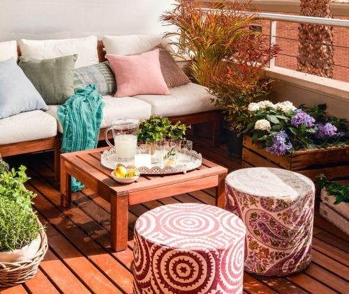 A small terrace decorated with furniture and plants.