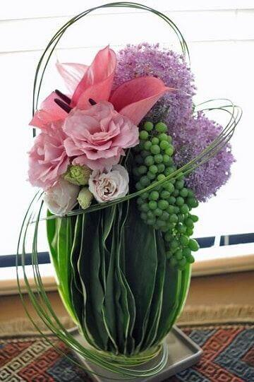 A flower arrangement with grapes.