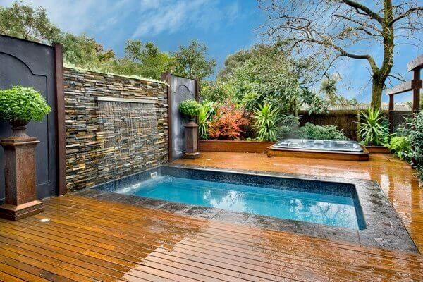 A backyard immersion pool with a waterfall decoration