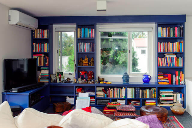 A home library with a dark blue wall.