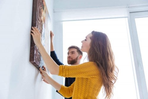 A couple hanging a painting on the wall.